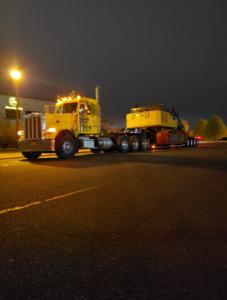 Heavy duty tow truck hauling construction equipment